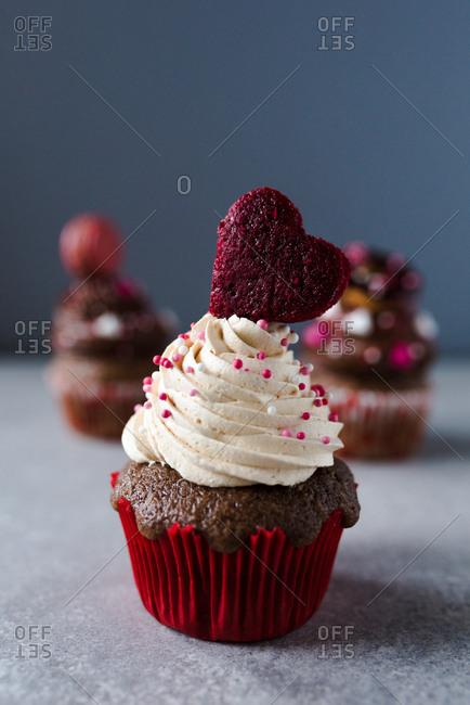 Close up of a Valentine's day themed cupcake with white cream and heart as decoration