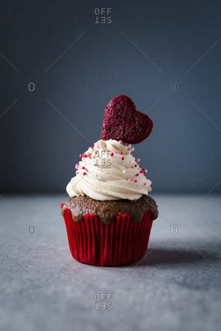 One Valentine's day themed cupcake with white cream and heart as decoration