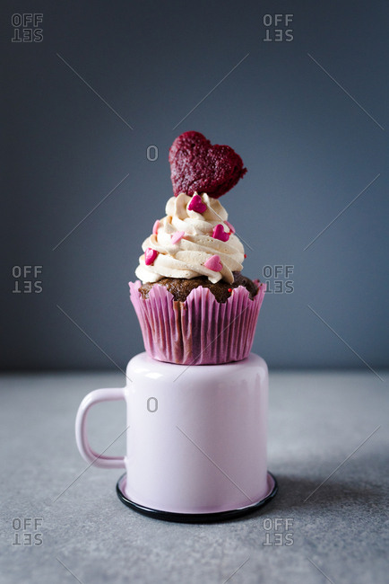 A Valentine's day themed cupcake with white cream and heart as decoration