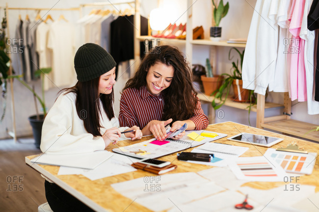 Smiling fashion designers working in their studio.