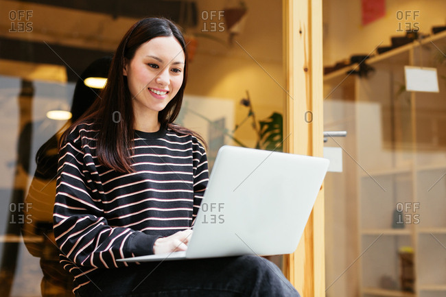 Fashion designer using laptop sitting by doorway.