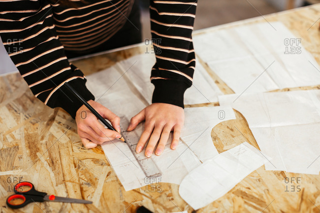 Anonymous designer working with sewing patterns in studio.