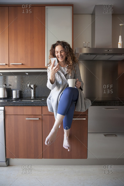 business woman with curly hair sitting in the kitchen taking an infusion while using her smart phone, working at home