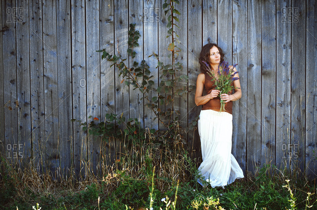 Pregnant woman holding wild flowers at the wooden wall