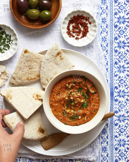 Muhammara with Pita Bread and Olives, and Someone's Hand