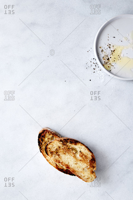 Two pieces of toast on table with a plate of olive oil and salt and pepper