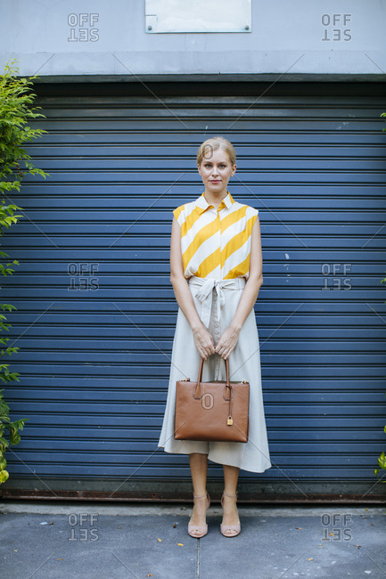 Portrait of beautiful Caucasian blonde elegant woman holding a purse and looking at camera.