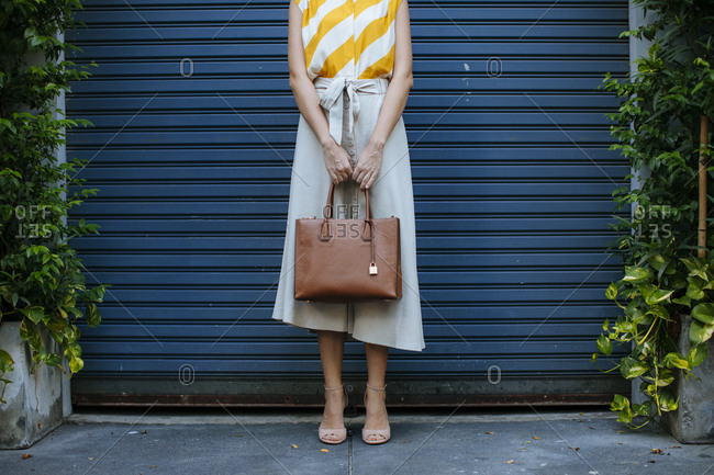 Unrecognisable elegant woman woman standing outdoors and holding a purse.