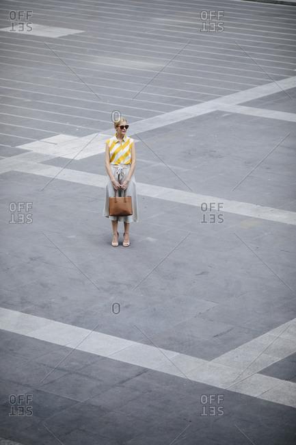 Elegant Caucasian businesswoman standing on the street.