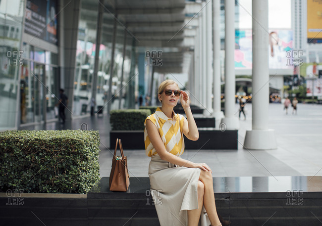Beautiful Caucasian woman sitting outdoors at the city and holding her sunglasses.