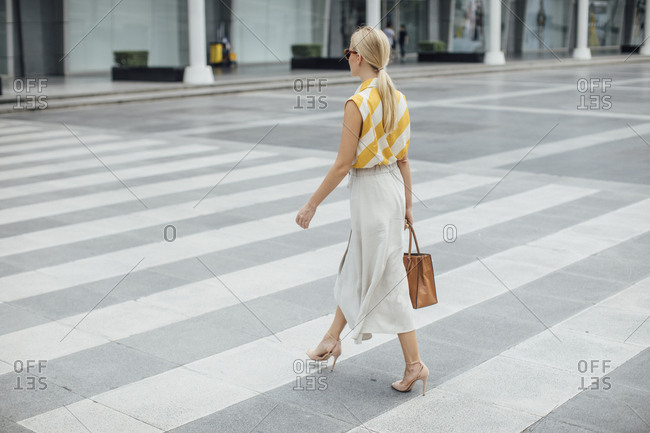 Beautiful elegant confident businesswoman walking on the street carrying a purse.