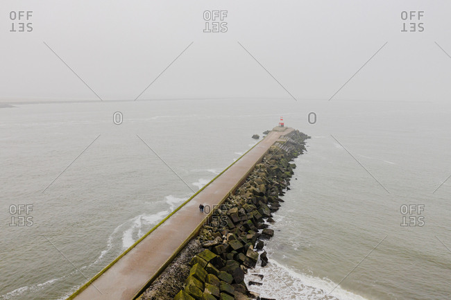 Tourists walk on pier leading into the North Sea in the Netherlands