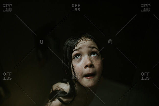 Little girl looking up while dripping wet in the shower