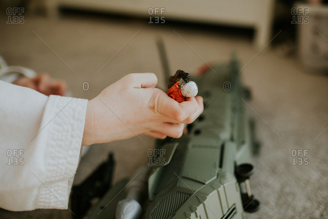 Little boy's hand holding a toy action figure