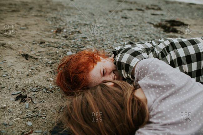 Two young girls lying on a beach laughing