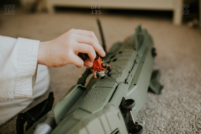 Little boy's hand playing with a toy plane and action figure