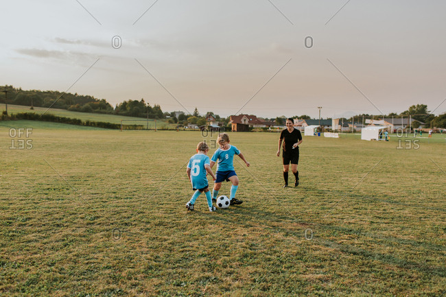 Boys playing football. Two soccer players  from same team kicking ball on field.