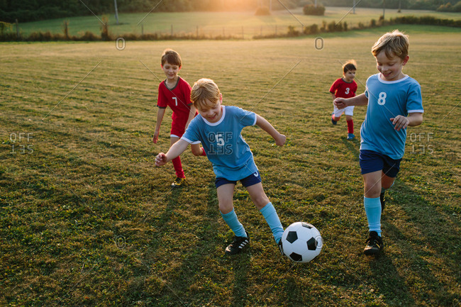 Children playing amateur soccer. Cheerful boys in football dresses having fun chasing ball outside on pitch at sunset.