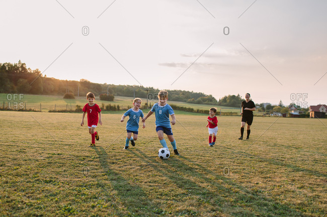 Children playing soccer. Full length of cheerful boys in football dresses chasing ball on field.