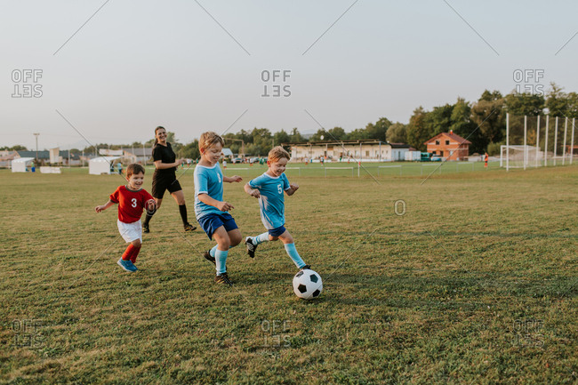 Children playing soccer. Group of happy football players running after ball on field.