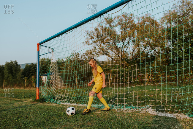 Girl goalkeeper defending goal. Full length of young girl footballer in yellow football dress kicking ball out of net.