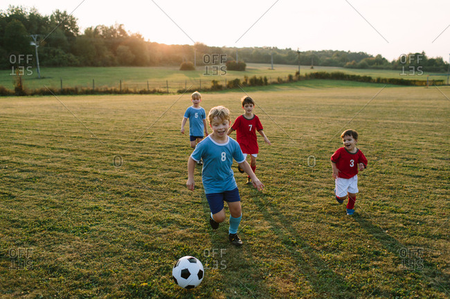 Children playing soccer. Cheerful boys in football dresses running after ball on field.