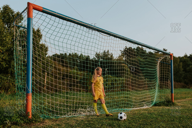 Girl goalkeeper standing at goal on soccer field. Full length of young teenage girl in yellow soccer dress with ball in front of football net.