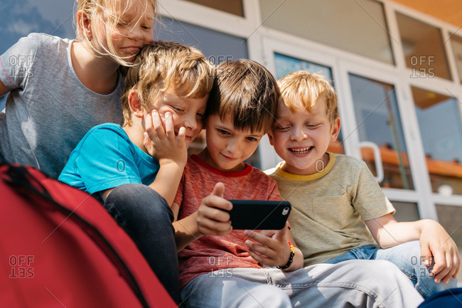 Young students playing with a mobile phone. Children having fun taking a selfie outside of school.