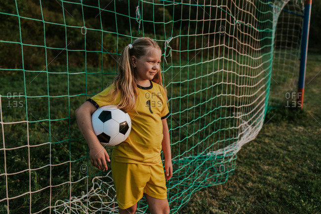 Girl goalkeeper standing at goal on soccer field. Girl in yellow football dress holding ball in front of football net.