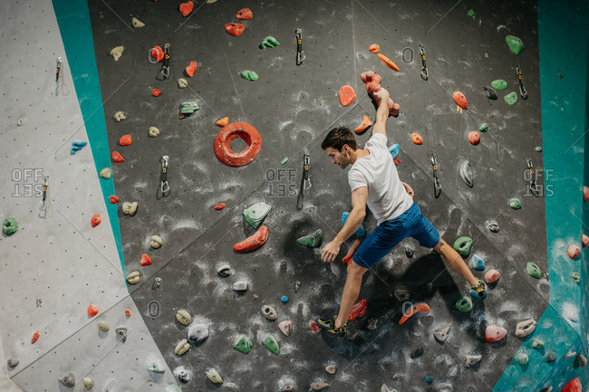 Back view of a male climber taking a rest while climbing up an artificial climbing wall in an indoor bouldering gym. Man making his way up a bouldering wall.