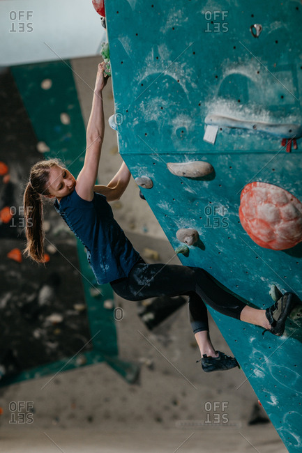 Female climber climbing up an artificial climbing wall in an indoor bouldering gym. Woman resting whilst making her way up a bouldering wall.
