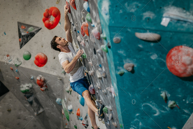 Male climber climbing up an artificial climbing wall in an indoor bouldering gym. Man making his way up a bouldering wall.