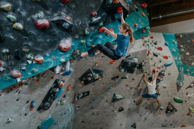 Man and woman climbing up an artificial climbing wall together. Couple of climbers in an indoor bouldering gym.
