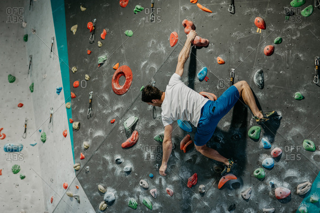 Back view of a male climber climbing up an artificial climbing wall in an indoor bouldering gym. Rear view of a man making his way up a bouldering wall.