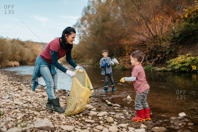 Woman cleaning up plastic waste with her young sons on river beach. Female volunteer and her children picking up trash in nature.