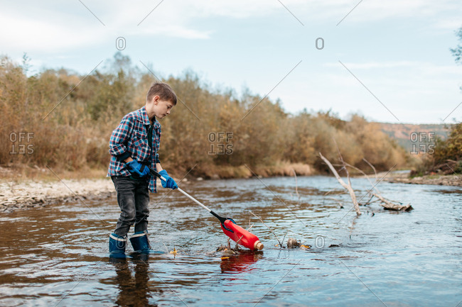 Young boy with trash picker standing in water and cleaning up plastic waste. Cleanup - child volunteer picking up plastic bottle from river.