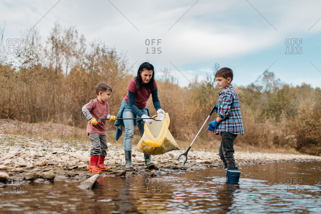 Woman cleaning up plastic waste with her young sons on river beach. Female volunteer and her children picking up trash from the water.