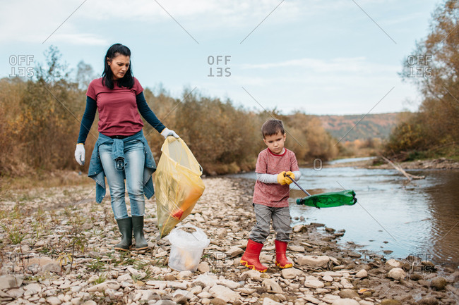 Mother and her toddler son picking up plastic bottles around river. Female volunteer and her child collecting garbage on river beach.