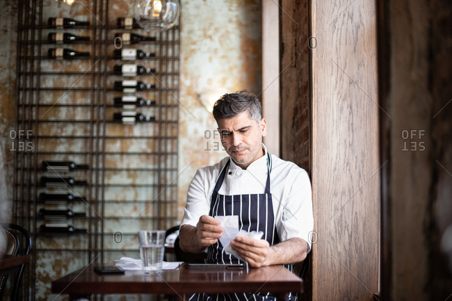 Male chef working on accounts in restaurant
