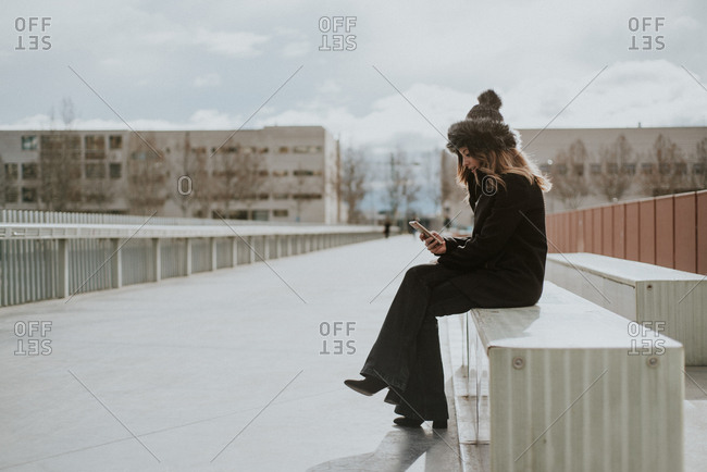 Woman sitting on a bench using cell phone