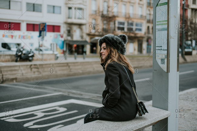Woman waiting at a bus stop