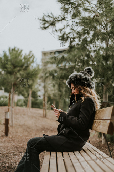 Fashionable young woman sitting on a park bench using cell phone