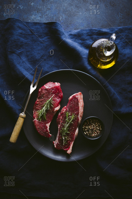 Two slices of raw seasoned sirloin overhead shot