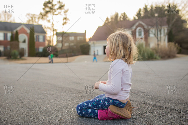 Little girl watching kids play outside