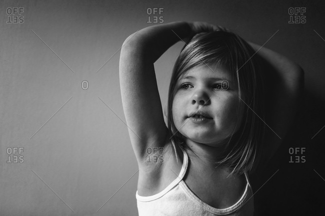 Little girl with her arms on her head