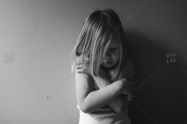 Little girl hugging herself