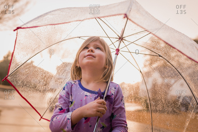 Little girl standing in the rain under a umbrella