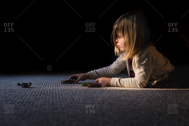 Little girl playing with toy cars