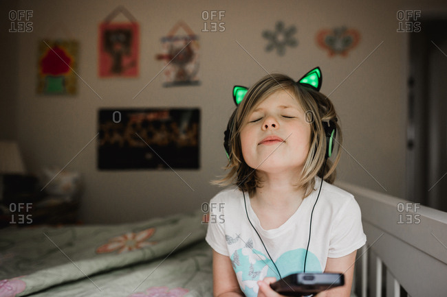 Little girl singing and listening to music stock photo - OFFSET