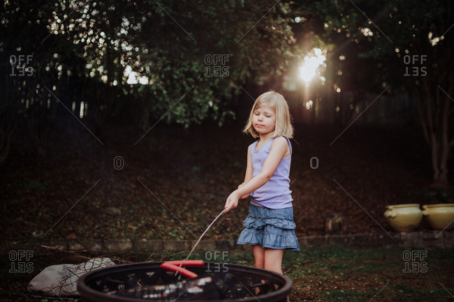 Little girl cooking hot dogs